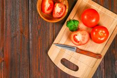 Fresh red tomatoes and sliced halves with cilantro on a wooden table. Top view. stock photos
