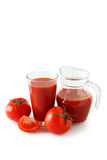 Fresh red tomatoes and tomato juice in glass and jug isolated on a white Royalty Free Stock Image