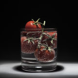 Fresh red tomatoes in water isolated on a black background. Bubbles of water. Branch of tomatoes. Royalty Free Stock Images