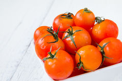 Fresh red tomatoes in white bowl on white wooden table Stock Photo