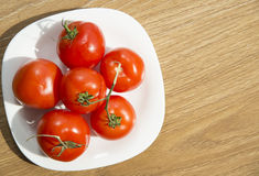 Fresh red tomatoes in white plate on wooden table Stock Photography