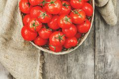 Fresh red tomatoes in a wicker basket on an old wooden table. Ripe and juicy cherry tomatoes with drops of moisture, gray wooden. Table, around a cloth of royalty free stock images