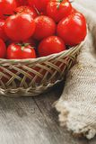 Fresh red tomatoes in a wicker basket on an old wooden table. Ripe and juicy cherry tomatoes with drops of moisture, gray wooden. Table, around a cloth of royalty free stock photos