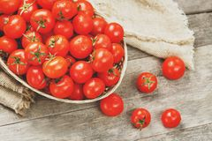 Fresh red tomatoes in a wicker basket on an old wooden table. Ripe and juicy cherry tomatoes with drops of moisture, gray wooden. Table, around a cloth of royalty free stock image
