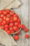 Fresh red tomatoes in a wicker basket on an old wooden table. Ripe and juicy cherry tomatoes with drops of moisture, gray wooden. Table, around a cloth of stock image