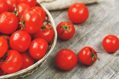 Fresh red tomatoes in a wicker basket on an old wooden table. Ripe and juicy cherry tomatoes with drops of moisture, gray wooden. Table, around a cloth of stock photo