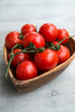 Fresh red tomatoes in wooden plate. Fresh red delicious tomatoes  in the heart shape wooden plate on an wooden tabletop Royalty Free Stock Images