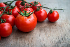 Fresh red tomatoes on wooden tabletop backgro Stock Photos