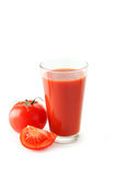 Fresh red tomatos and full glass Stock Images