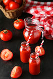 Fresh red tomatos and juice in bottles and jug on a black background Royalty Free Stock Photo