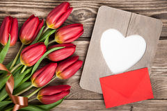 Fresh red tulips, blank frame and envelope Royalty Free Stock Image