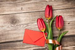 Fresh red tulips and envelope. On wooden background Stock Images