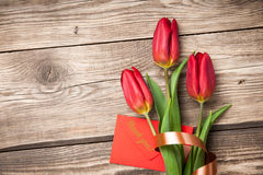 Fresh red tulips and envelope. On wooden background Royalty Free Stock Image