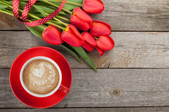 Fresh red tulips with ribbon and coffee cup with heart shape Royalty Free Stock Photography