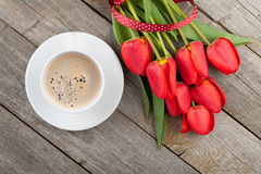 Fresh red tulips with ribbon and coffee cup Royalty Free Stock Image