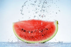 Fresh red watermelon slice with splash and drops of water Royalty Free Stock Image