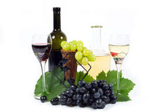 Fresh Red and White Grapes with Green Leaves, Two Wine Glass Cups and Wine Bottles Filled with Red and White Wine  Isolated Royalty Free Stock Photography