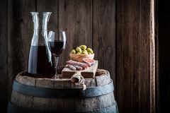 Fresh red wine with cold meats and olives on old barrel Royalty Free Stock Image