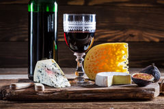 Fresh red wine with grapes and cheese. On old wooden table Royalty Free Stock Photography