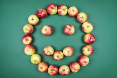 Fresh red and yellow apples forming smiling face on green background. stock image