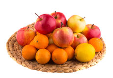 Fresh red and yellow apples, tangerines and lemons in a wooden basket Royalty Free Stock Photo