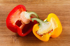 Fresh red and yellow bell pepper, cut one on wooden background Royalty Free Stock Images