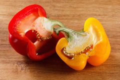 Fresh red and yellow bell pepper, cut one on wooden background Royalty Free Stock Photo