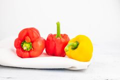 Fresh red and yellow bell peppers on a white wooden background. stock image