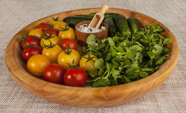Fresh red and yellow cherry tomatoes and cucumbers, onions on a wooden tray in a rustic style. Stock Photo