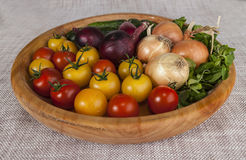 Fresh red and yellow cherry tomatoes and cucumbers, onions on a wooden tray in a rustic style. Stock Photography