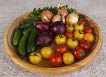 Fresh red and yellow cherry tomatoes and cucumbers, onions on a wooden tray in a rustic style. Royalty Free Stock Photos