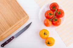 Fresh red and yellow tomatoes from above on a white textured table with a board and a knife. Fresh red and yellow tomatoes from above on a white textured table Stock Photos