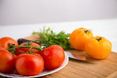 Fresh red and yellow tomatoes close up on a wooden board with a knife. At a white textured table Royalty Free Stock Photography