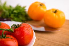 Fresh red and yellow tomatoes close up on a wooden board with a knife. At a white textured table Stock Images