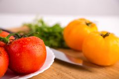 Fresh red and yellow tomatoes close up on a wooden board with a knife at a white table. Fresh red and yellow tomatoes close up on a wooden board with a knife at Stock Photo