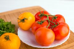 Fresh red and yellow tomatoes close up on a wooden board at a white table. Fresh red and yellow tomatoes close up on a wooden board at a white textured table Royalty Free Stock Photography