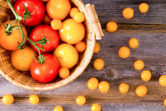 Fresh red and yellow tomatoes. Some on the vine, displayed in a rustic woven wicker basket on a wooden table with scattered cherry tomatoes, overhead view stock images