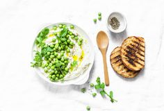 Fresh ricotta cheese with green peas, olive oil, pepper and herbs on a light background, top view. Healthy diet food - delicious b. Reakfast, snack, appetizers royalty free stock images