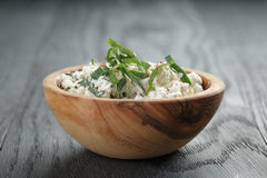 Fresh ricotta with herbs in olive wood bowl on old Royalty Free Stock Image