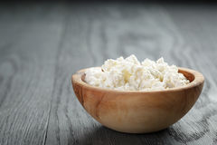 Fresh ricotta in olive wood bowl on old table Stock Image