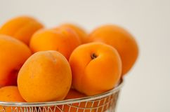 Fresh ripe  apricots are  in the basket. On white background Royalty Free Stock Photo