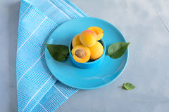 Fresh and ripe apricots on grey background. Season berries, summer food. Some fresh and ripe apricots on the table colored in grey, decorated with napkins Stock Photography