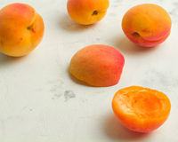 Fresh and ripe apricots on a white stone background. Side view Royalty Free Stock Image