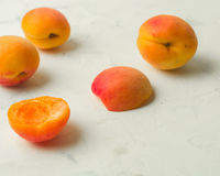 Fresh and ripe apricots on a white stone background. Side view Stock Images