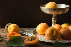 Various Fresh ripe apricots on wooden surface leaves fruits apricots on board cut apricots in half. Light blue rustic wood backgro. Fresh ripe apricots on wooden Stock Images