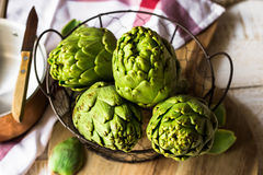 Fresh ripe artichokes in wire basket on wood kitchen table, linen napkin, top view. Close up Stock Photo