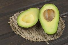 Fresh ripe avocado on a wooden background. Food background with fresh organic avocado. Royalty Free Stock Photo