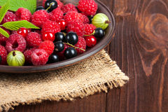 Fresh ripe berries in the bowl on the old wooden table. Useful natural food. Stock Photo