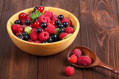 Fresh ripe berries in the bowl on the old wooden table. Useful natural food. Royalty Free Stock Photography