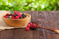 Fresh ripe berries in the bowl on the old wooden table. Useful natural food. Stock Photos
